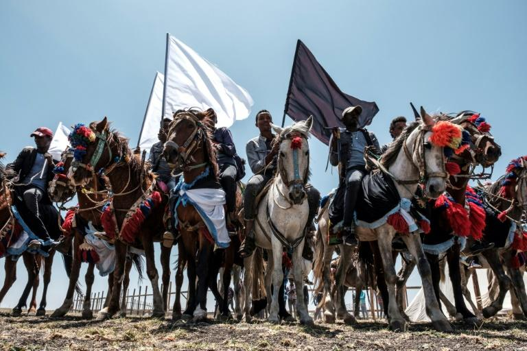 Horsemen carried black and white flags as they rode around the crash site