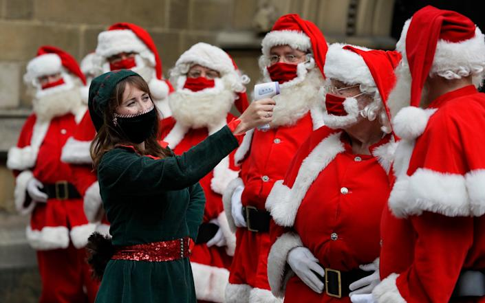 Santas have their temperature taken as they attend a socially distanced Santa school training at Southwark Cahedral in London, Monday, Aug. 24, 2020 - Kirsty Wigglesworth