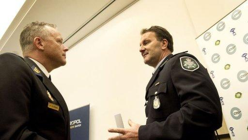 "Dutch Joop Scheffer (L) of the Zaanstreek-Waterland police department talks with Australian colleague Grant Edwards before a press conference in The Hague. Police in several countries have arrested scores of alleged members of an online paedophile ring and rescued 230 children in ""the biggest case of its kind"", Europol said on Wednesday"