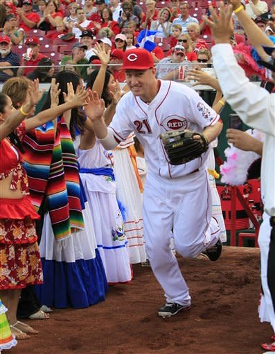 Cincinnati Reds' Todd Frazier high-fives dancers from Central and South America as he runs onto the field at the start of a baseball game against the Houston Astros, Friday, Sept. 7, 2012, in Cincinnati. The costumed dancers were part of Hispanic Heritage Night events at the ballpark. (AP Photo/Al Behrman)