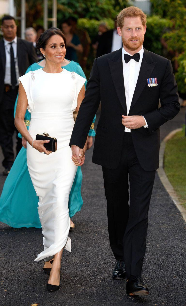 """<p>For their first official engagement in Tonga, Meghan Markle stunned in a floor-length white gown by New York designer <a href=""""https://theiacouture.com/"""" rel=""""nofollow noopener"""" target=""""_blank"""" data-ylk=""""slk:Theia"""" class=""""link rapid-noclick-resp"""">Theia</a>.</p><p>The dress featured embellished details on the shoulder and was teamed with a beautiful aquamarine ring from her late mother-in-law Princess Diana's collection, which appears to be the <a href=""""https://www.elle.com/uk/fashion/celebrity-style/a20134181/meghan-markle-second-royal-wedding-dress-stella-mccartney-reception/"""" rel=""""nofollow noopener"""" target=""""_blank"""" data-ylk=""""slk:same ring she wore with her Stella McCartney dress for her royal wedding reception"""" class=""""link rapid-noclick-resp"""">same ring she wore with her Stella McCartney dress for her royal wedding reception</a>.</p><p>She teamed the look with her favourite <a href=""""https://www.lyst.co.uk/track/lead/535409588/return/?atc_medium=cpc&atc_source=google&atc_campaign=UK-PLA-CSS&atc_content=UK-PLA-Aquazzura%2BHeels-Clothing%2B%2526%2BAccessories%2B%253E%2BShoes%2B%253E%2BHigh%2BHeel%2BShoes%2B%253E%2BBasic%2BPumps-CSS%2BUlloa-no&atc_country=UK&atc_grouping=Google-PLA-CSS&reason=pla-css&sem_id=A849914533"""" rel=""""nofollow noopener"""" target=""""_blank"""" data-ylk=""""slk:Aquazzura Deneuve heels"""" class=""""link rapid-noclick-resp"""">Aquazzura Deneuve heels</a>, a Givenchy clutch bag and Birds earrings.</p>"""