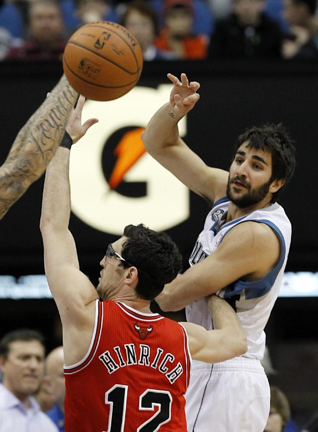 Minnesota Timberwolves guard Ricky Rubio, right, of Spain, passes to a teammate under pressure from Chicago Bulls guard Kirk Hinrich (12) during the first quarter of an NBA basketball game in Minneapolis, Wednesday, April 9, 2014. (AP Photo/Ann Heisenfelt)