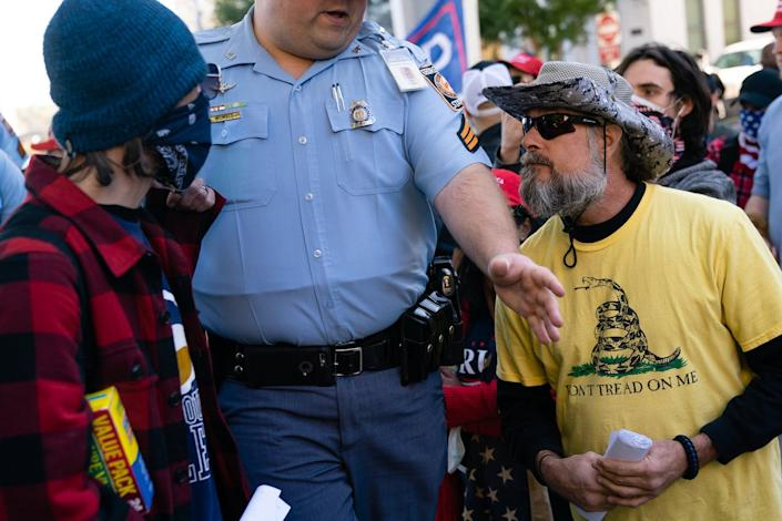 A Georgia state trooper separates Biden supporters from Trump supporters.