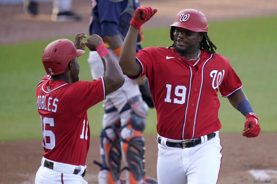 Washington Nationals' Josh Bell (19) is met by Victor Robles (16) after hitting a two-run home run during the first inning of a spring training baseball game against the Houston Astros, Wednesday, March 24, 2021, in West Palm Beach, Fl. (AP Photo/Lynne Sladky)