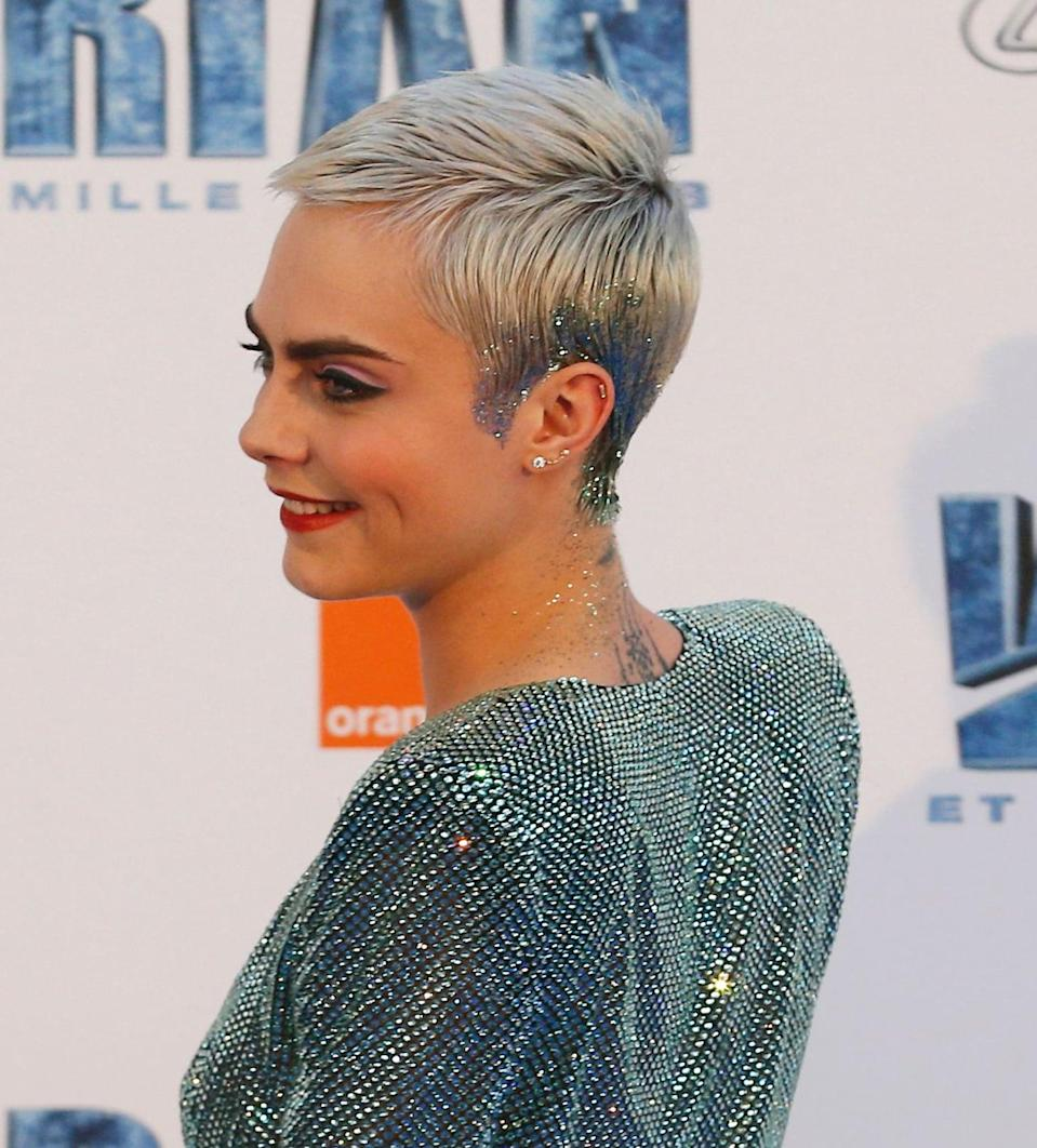 <p>Delevingne used loose glitter as a way to dress up her classic pixie cut, which at the time was too short for most barrettes and hair baubles. The aquamarine-colored sparkle started along the bottom half of her hair - encircling her ear - and extended right down her neck, creating a seamless stretch of sparkle from head to toe.</p>