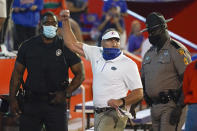 Florida head coach Dan Mullen, center, raises his fist to cheering Florida fans after an argument at the end of the first half as he was escorted to the locker room by law enforcement officers during an NCAA college football game against Missouri, Saturday, Oct. 31, 2020, in Gainesville, Fla. (AP Photo/John Raoux)