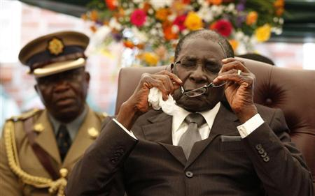 Zimbabwe President Robert Mugabe holds his glasses during the funeral of his sister, Bridget, in the village of Zvimba