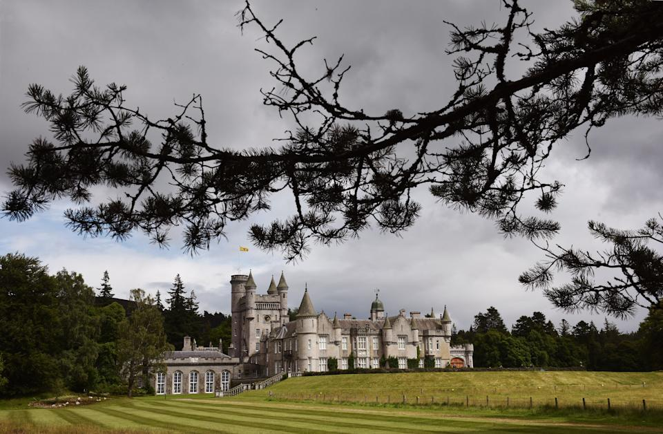 Crathie, UK - July 29th 2015: Scottish fir trees frame the distant view of Balmoral Castle.