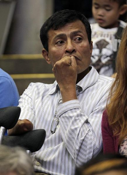 Myo Myint, a political prisoner for 15 years, listens as Myanmar democracy leader Aung San Suu Kyi speaks in Fort Wayne, Ind., Tuesday, Sept. 25, 2012. (AP Photo/Michael Conroy)