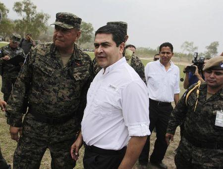 Honduras' President Hernandez talks to officers of Honduras' army during a presentation in Mateo