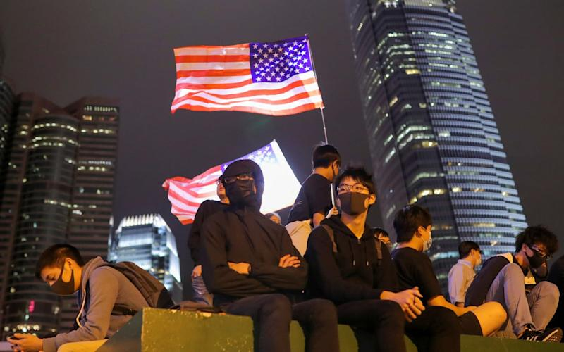 Protesters sit next to a U.S. flag as they attend a gathering at the Edinburgh place in Hong Kong, China, November 2 - REUTERS