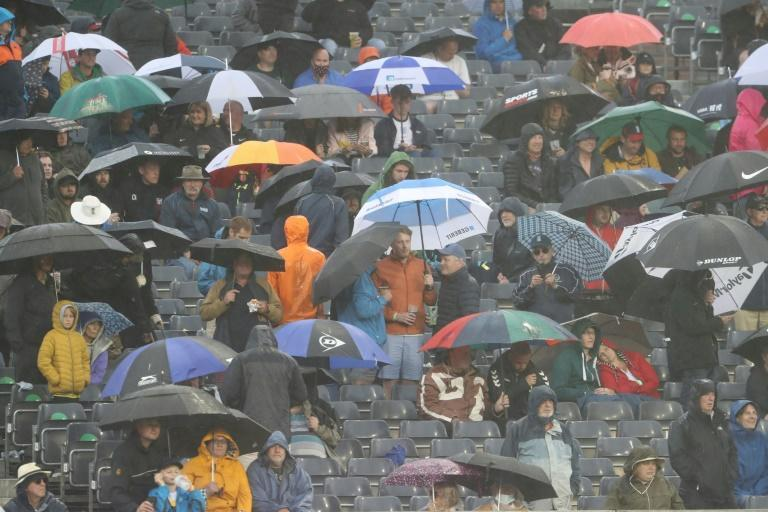 Washout - Spectators shelter under umbrellas from the rain that ended the match at Bristol