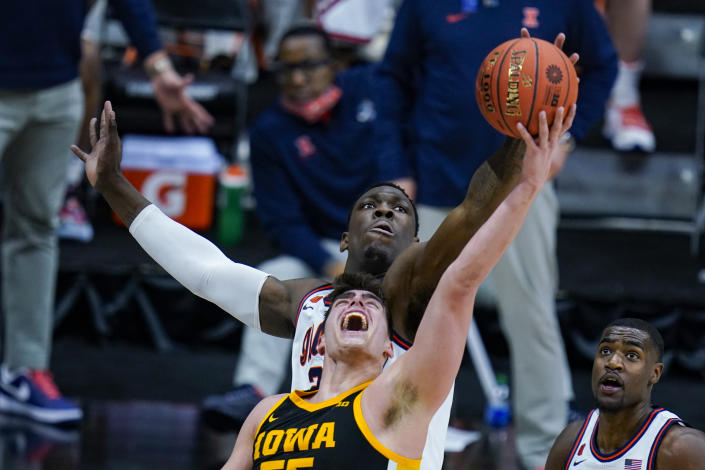 Illinois center Kofi Cockburn, top, blocks a shot over Iowa center Luka Garza, bottom, in the first half of an NCAA college basketball game at the Big Ten Conference tournament in Indianapolis, Saturday, March 13, 2021. (AP Photo/Michael Conroy)