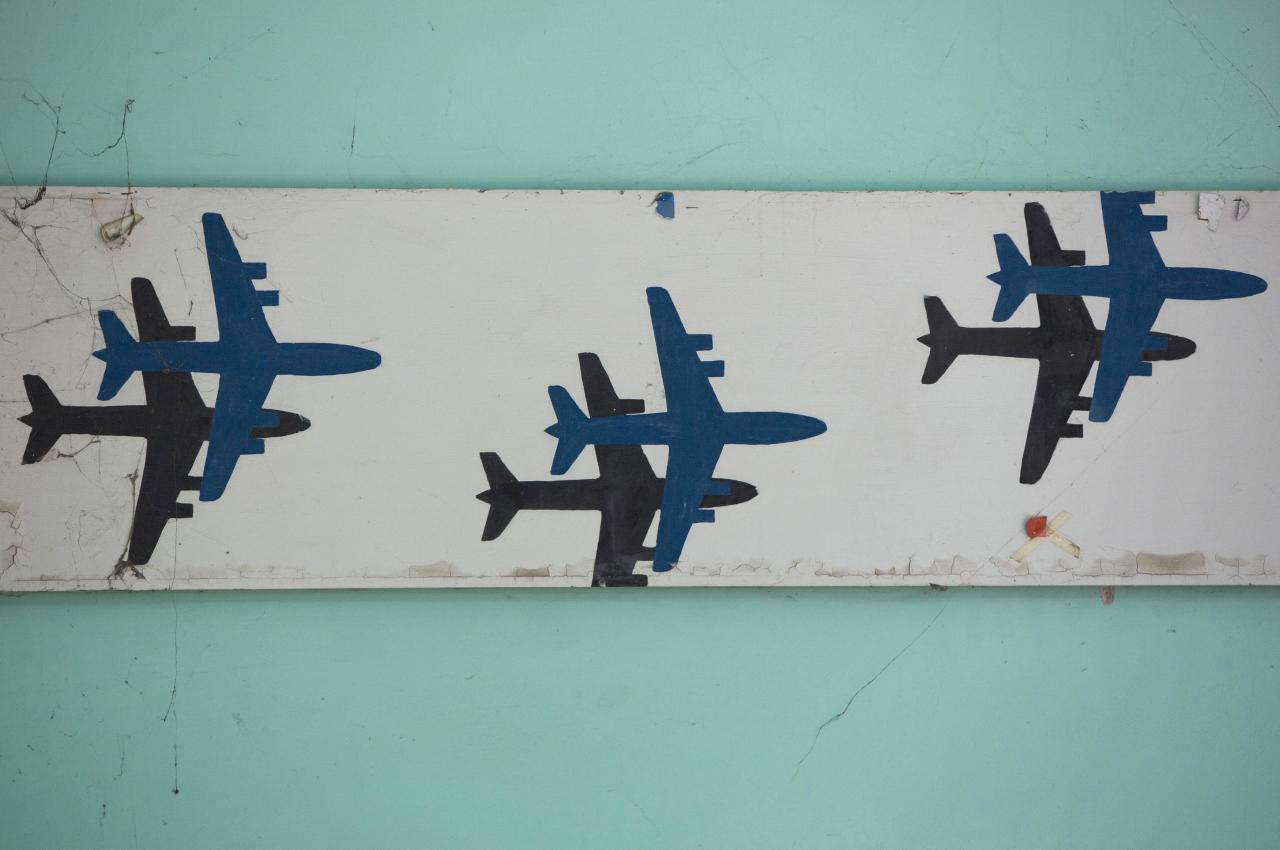 Images of aeroplanes decorate a wall at the abandoned Nicosia International Airport near Nicosia March 10, 2014. Greek and Turkish Cypriots have lived estranged for decades. A power-sharing government crumbled soon after independence from Britain in 1960 and the island has been divided since a Greek Cypriot coup was followed by a Turkish invasion of the north in 1974. Four decades on, a United Nations-controlled buffer zone splits Cyprus east to west, with Cyprus's ethnic Greeks living in the south, and its Turks in the north. The buffer zone still contains crumbling relics of times gone by - abandoned houses, businesses and even an airport. Picture taken March 10, 2014. REUTERS/Neil Hall (CYPRUS - Tags: POLITICS SOCIETY TRANSPORT)