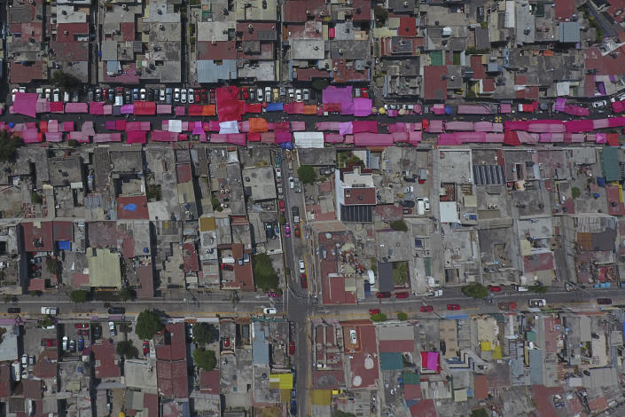 Stalls shielded from the sun with pink awnings line a road during a reduced, but still active weekly street market in northern Mexico City, Sunday, March 29, 2020, as many people stay home amid the spread of the new coronavirus. (AP Photo/Rebecca Blackwell)