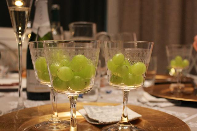 <p>The Spanish kick off their New Year's health resolution by eating 12 grapes at midnight. But it's harder than it sounds – because you have to eat one grape each time the bell tolls. It's said that if you're successful, you'll have a year of prosperity. The best place to experience the so-called Twelve Grapes ritual is the Puerta del Sol in Madrid, where crowds have 12 grapes in one hand and a glass of cava in the other. [Photo: Flickr/Chris Oakley] </p>