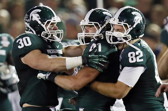 Michigan State running back Riley Bullough, left, and tight end Josiah Price, right, congratulate linebacker Kyler Elsworth after he helped stop Stanford on fourth down during Stanford's final drive of the Rose Bowl NCAA college football game on Wednesday, Jan. 1, 2014, in Pasadena, Calif. Michigan State won 24-20. (AP Photo/Danny Moloshok)