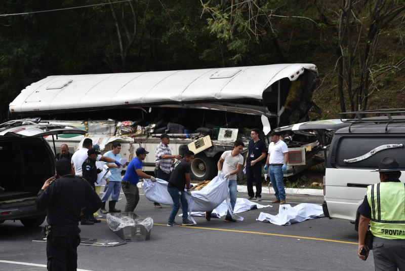 Rescue workers carry body bags with the remains of passengers after a deadly bus accident in Gualan, Guatemala, Saturday, Dec. 21, 2019. The accident killed at least 21 people and left a dozen wounded, according to the national disaster agency. (AP Photo/Carlos Cruz)