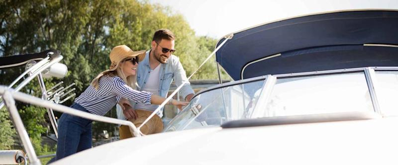 A beautiful young couple watches a motor boat that they intend to buy.