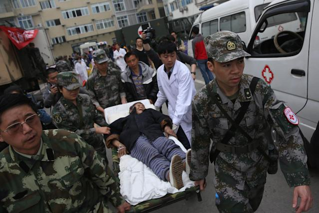 CHENGDU, CHINA - APRIL 22: The military medical officers carry a patient to an ambulance at the hospital on April 22, 2013 in Lushan of Ya An, China. A magnitude 7 earthquake hit China's Sichuan province on April 20 claiming over 180 lives and injuring thousands. (Photo by Feng Li/Getty Images)