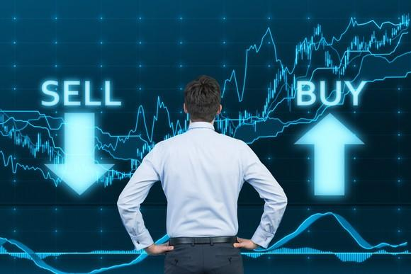 A businessman looking at a stock chart with arrows labeled SELL and BUY