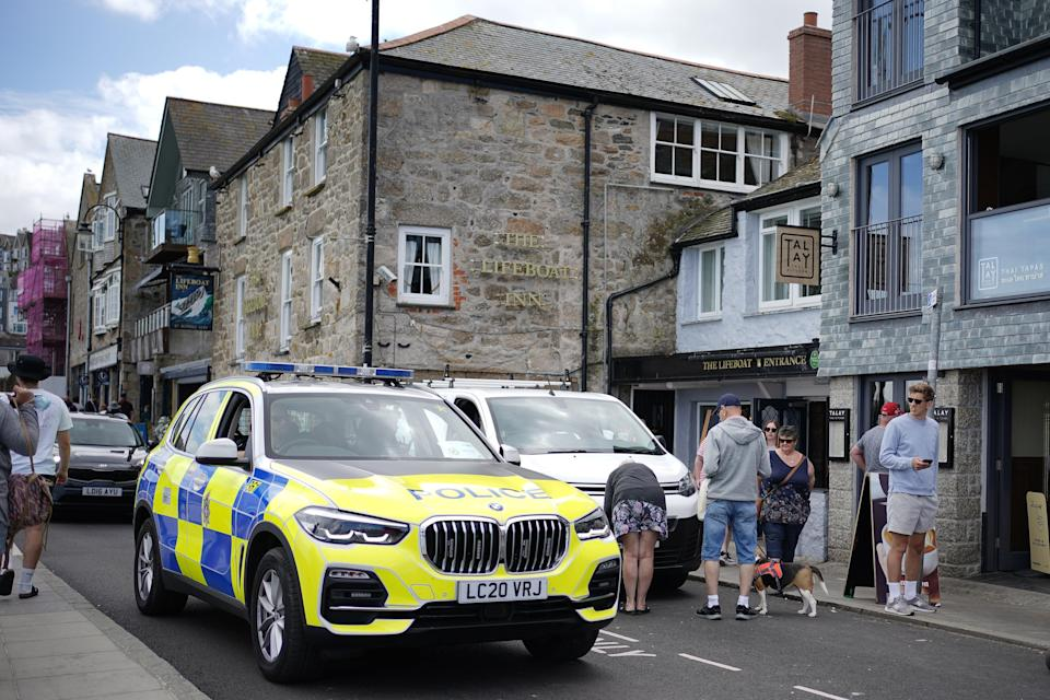 A police vehicle driving in St Ives harbour (PA)