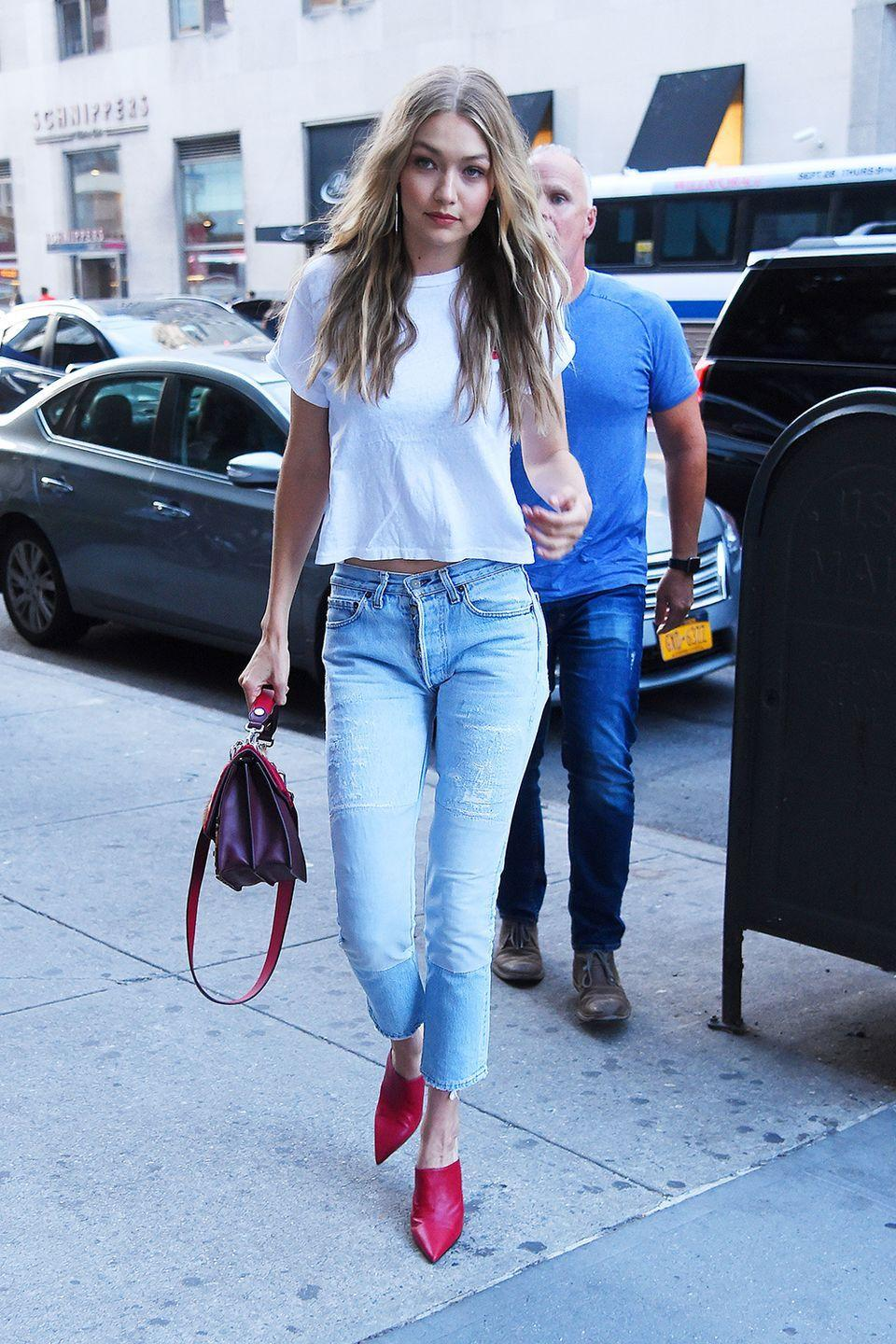 <p>In a white t-shirt with cropped jeans and red leather mules while out in New York City.</p>