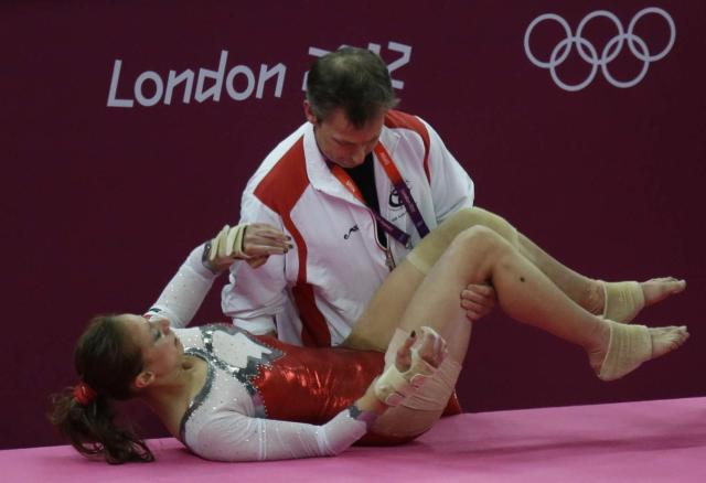 Egypt's gymnast Sherine Ahmed Elzeiny is carried by her coach after she sustained an injury during the Artistic Gymnastic women's qualifications at the 2012 Summer Olympics, Sunday, July 29, 2012, in London. (AP Photo/Julie Jacobson)