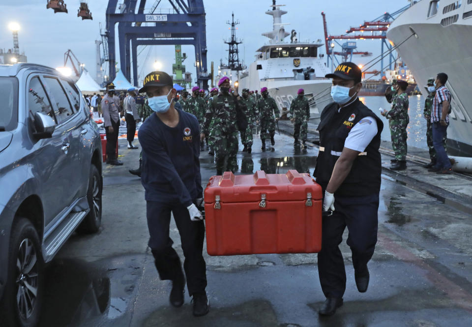 Members of the National Transportation Safety Committee carry a box containing the flight data recorder of Sriwijaya Air flight SJ-182 retrieved from the Java Sea where the passenger jet crashed at the Tanjung Priok Port, Tuesday, Jan. 12, 2021. Indonesian navy divers searching the ocean floor on Tuesday recovered the flight data recorder from a Sriwijaya Air jet that crashed into the Java Sea with 62 people on board, Saturday, Jan. 9, 2021. (AP Photo/Dita Alangkara)