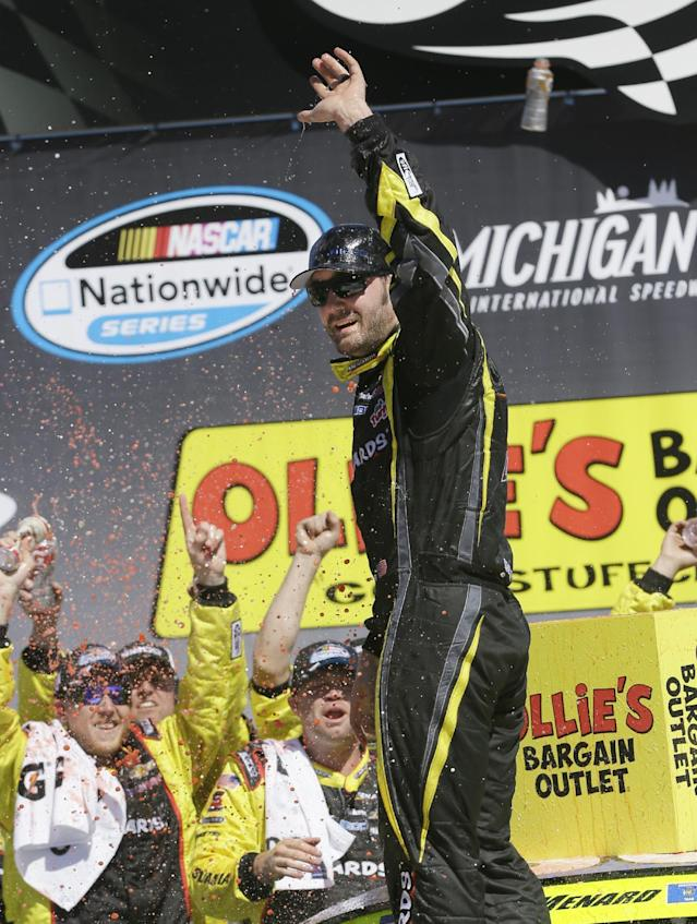 Driver Paul Menard acknowledges the crowd as he celebrates in Victory Lane after winning the NASCAR Nationwide series auto race at Michigan International Speedway in Brooklyn, Mich., Saturday, June 14, 2014. (AP Photo/Carlos Osorio)