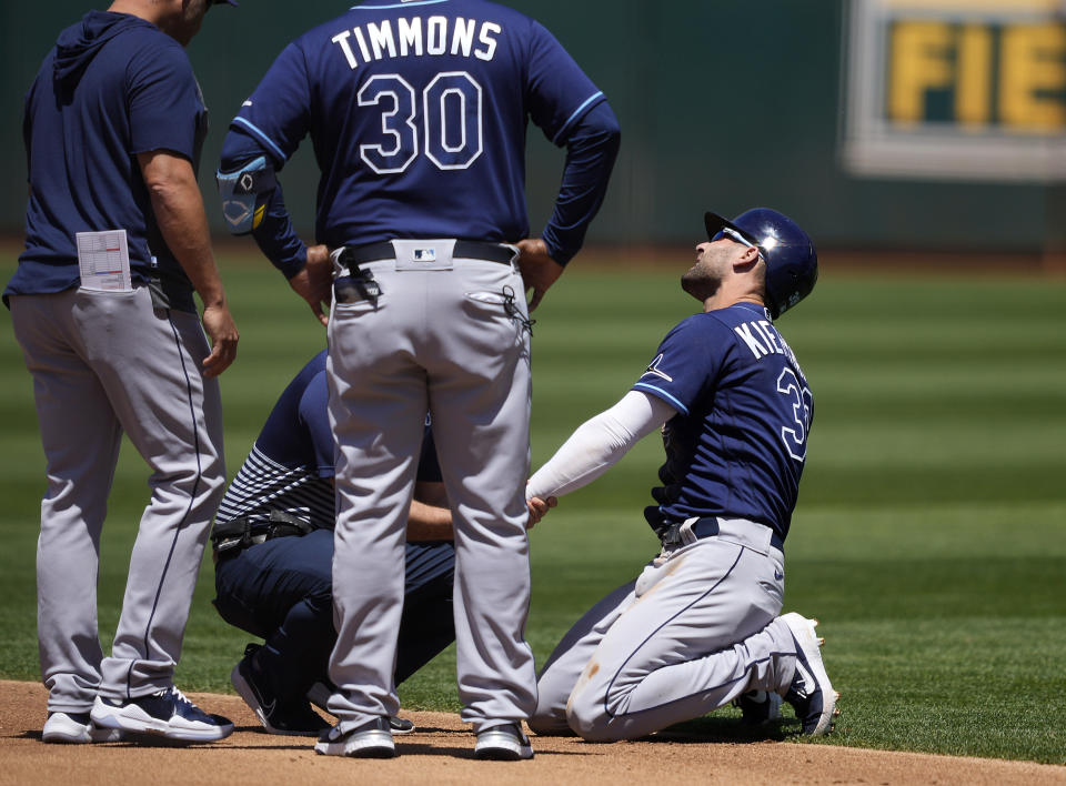 Tampa Bay Rays' Kevin Kiermaier, right, is looked at by a trainer after stealing second base during the second inning of a baseball game against the Oakland Athletics, Saturday, May 8, 2021, in Oakland, Calif. (AP Photo/Tony Avelar)