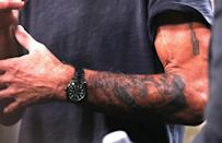 """<p>Bourdain's """"bad-boy chef"""" image didn't just come from his past — his sharp tongue and tatted-up skin added to it as well. In addition to the chef's knife, he had a skull on his right shoulder and an ouroboros — a snake swallowing its tail — on his left shoulder that he got while filming <em>No Reservations</em> in Malaysia. There was also one on his arm that reads """"I am certain of nothing,"""" in ancient Greek, and a scorpion tat that he got at a house party while filming <em>Parts Unknown</em> in Nashville.</p>"""