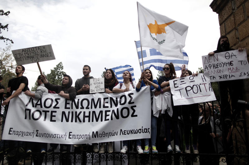 Cypriot students shout slogans as they stand at the entrance of the presidential palace in capital Nicosia, on Tuesday, March 26, 2013. The banner on the left reads in Greek ''people united never divided''. Banks across Cyprus remain firmly padlocked Tuesday after financial authorities extended the country's bank closure, fearing worried depositors will rush to drain their accounts. The shut-down is hammering businesses, which have been without access to their funds for more than a week.(AP Photo/Petros Giannakouris)