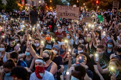 Protestors in Washington hold up their phones at a march on June 3