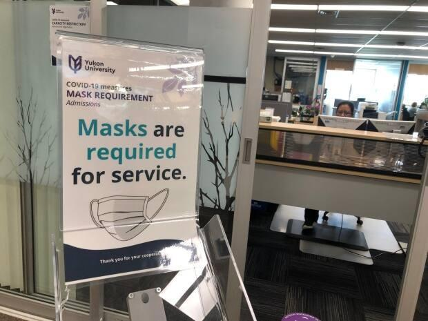 A sign requiring masks to be worn at Yukon University in November 2020. The Yukon is coping with its 'first wave' of COVID-19 since the pandemic began, despite its highly vaccinated population.  (Laura Howells/CBC - image credit)