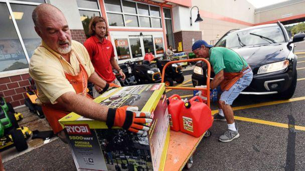 PHOTO: Jim Craig, David Burke and Chris Rayner load generators as people buy supplies at The Home Depot on Monday, Sept. 10, 2018, in Wilmington, N.C. (Ken Blevins/The Star-News via AP)