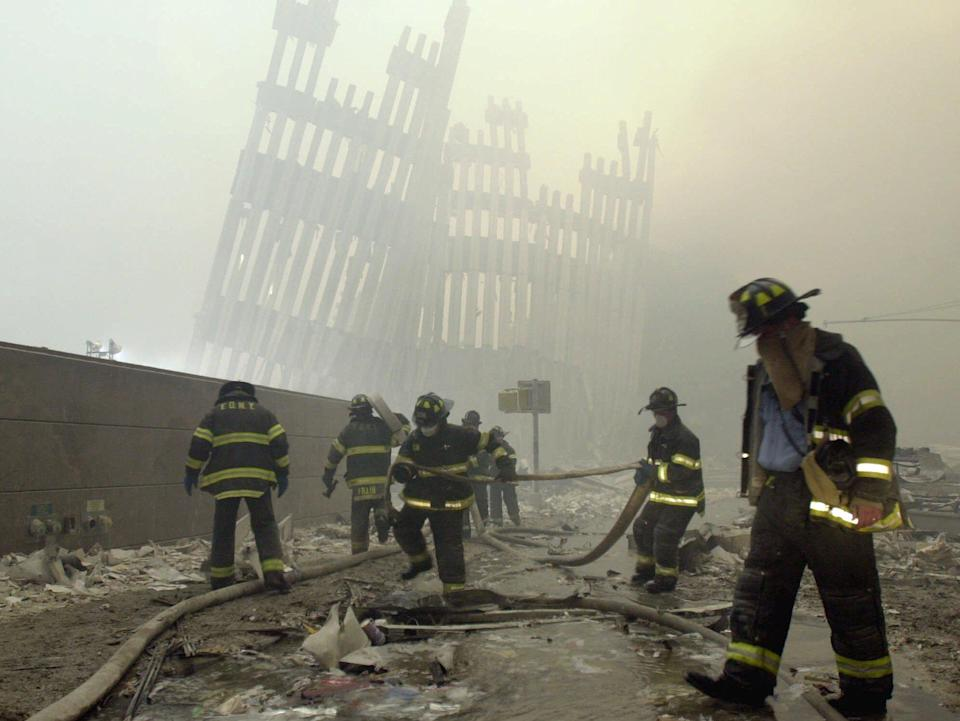 <p>With the skeleton of the World Trade Center twin towers in the background, New York City firefighters work amid debris on Cortlandt Street after the terrorist attacks in this Sept. 11, 2001, photo. (Photo:Mark Lennihan/AP) </p>
