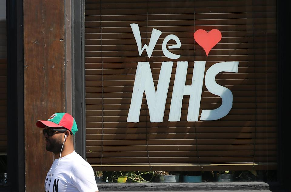 """A man walks past a message reading """"We love NHS"""" in the window of a closed-down pub outside The Royal London Hospital in Whitechapel, east London on Saturday. (PA)"""