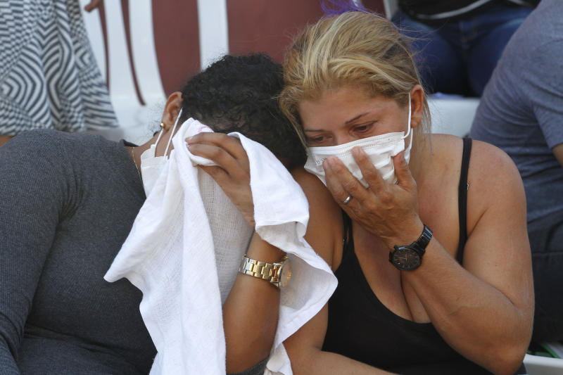 A woman wait outside the coroner's office in Altamira, Brazil, Tuesday, July 30, 2019. Relatives of inmates killed during a prison riot in northern Brazil gathered at the coroner's office Tuesday to identify the 57 victims, with some passing out at seeing the beheaded corpse of a loved one. (AP Photo/Raimundo Pacco)