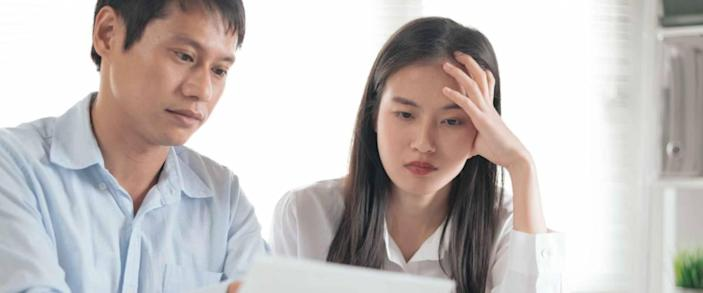 Young couple looking at a sheet of paper, looking concerned