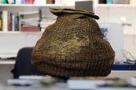 An ancient complete basket, part of various artefacts recently discovered in the Judean Desert caves along with scroll fragments of an ancient biblical texts, is seen during an event for media at Israel Antiquities Authority laboratories in Jerusalem
