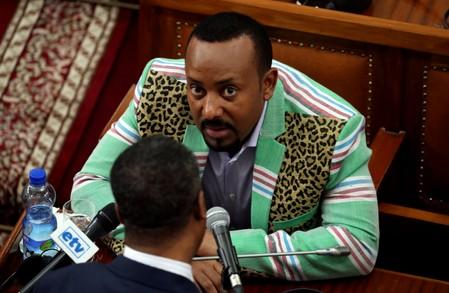 FILE PHOTO: Ethiopia's Prime Minister Abiy Ahmed talks to an unidentified legislator inside the House of Peoples' Representatives in Addis Ababa