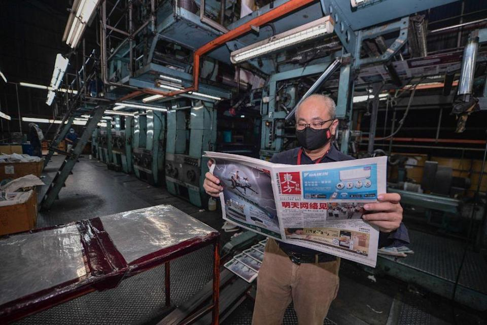Editor-in-chief of Oriental Daily Ding Lee Leong reads a copy of the final edition of the newspaper April 16, 2021. — Picture courtesy of Oriental Daily