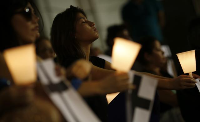 People hold candles as they attend a memorial by non-governmental organization (NGO) Rio de Paz (Rio of Peace), held in memory of police officers from the Police Peacekeeping Unit (UPP) who were killed while carrying out their duty, in downtown Rio de Janeiro March 17, 2014. The introduction of the peacekeeping program in the Rio de Janeiro slums is part of efforts to crack down on crime and increase security as the city prepares to host the 2014 World Cup soccer tournament and the 2016 Olympic Games. REUTERS/Sergio Moraes (BRAZIL - Tags: SOCIETY CIVIL UNREST CRIME LAW SPORT SOCCER WORLD CUP)