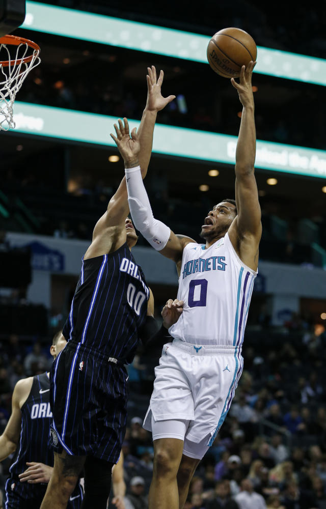 Charlotte Hornets forward Miles Bridges, right, shoots over Orlando Magic forward Aaron Gordon in the first half of an NBA basketball game in Charlotte, N.C., Monday, Jan. 20, 2020. (AP Photo/Nell Redmond)