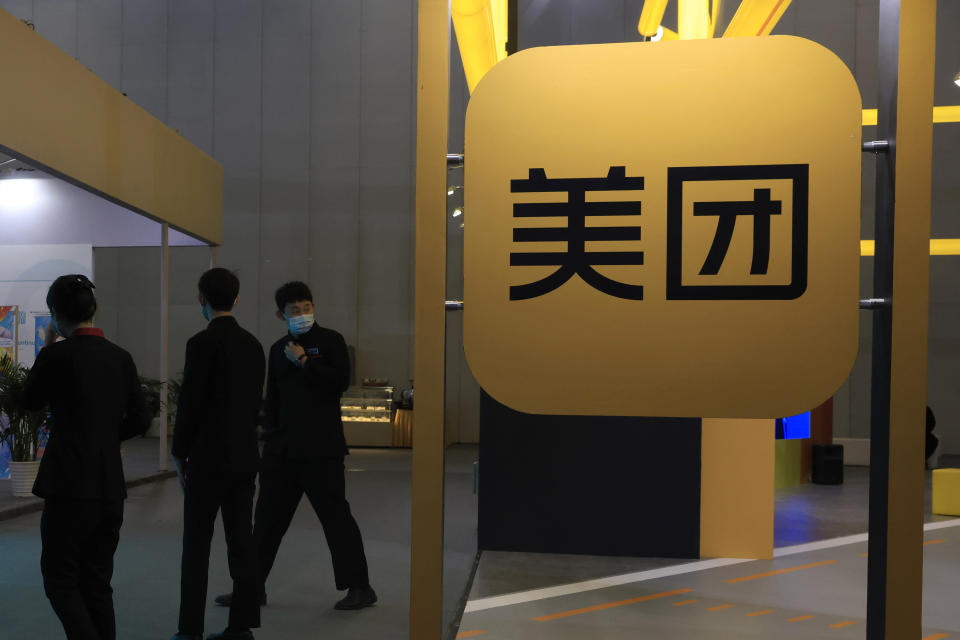 FILE - In this April 30, 2021, file photo, workers walk by the logo of Meituan during an Internet Technology Expo in Beijing. Shares in Meituan, China's largest food delivery platform, have tumbled Tuesday, May 11, 2021 after its CEO posted -and then deleted - an ancient poem in a move widely seen as criticism of the Chinese government. Authorities are investigating the company over allegations of anti-monopolistic behavior, part of a wider crackdown on technology companies. (AP Photo/Ng Han Guan, File)