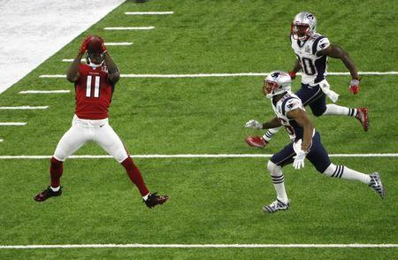 Atlanta Falcons' Jones makes a catch for a gain of 19 yards as New England Patriots' Ryan and Harmon look on during the second quarter at Super Bowl LI in Houston