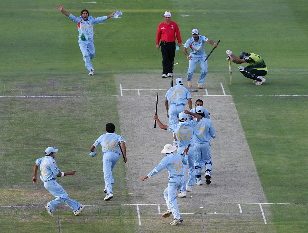 JOHANNESBURG, SOUTH AFRICA - SEPTEMBER 24:  The Indian Team celebrate their win with Misbah-ul-Haq looking on after the Twenty20 Championship Final match between Pakistan and India at The Wanderers Stadium on September 24, 2007 in Johannesburg, South Africa.  (Photo by Hamish Blair/Getty Images)