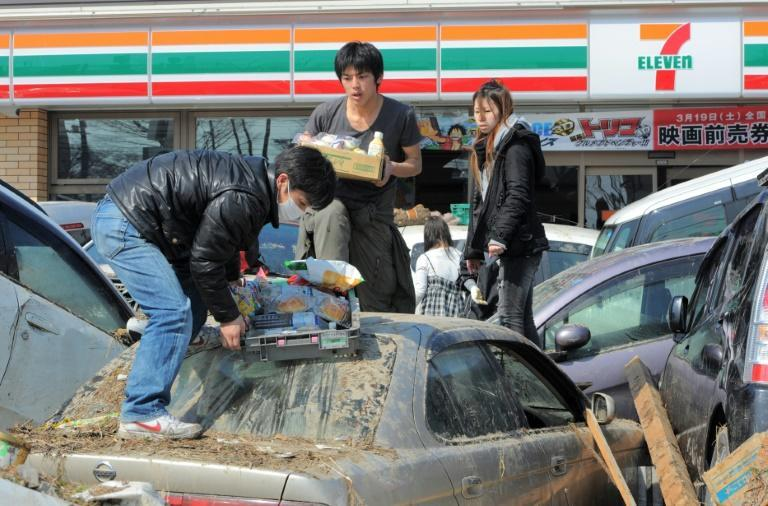 Residents carry outside a shop in Miyagi prefecture, two days after the tsunami hit