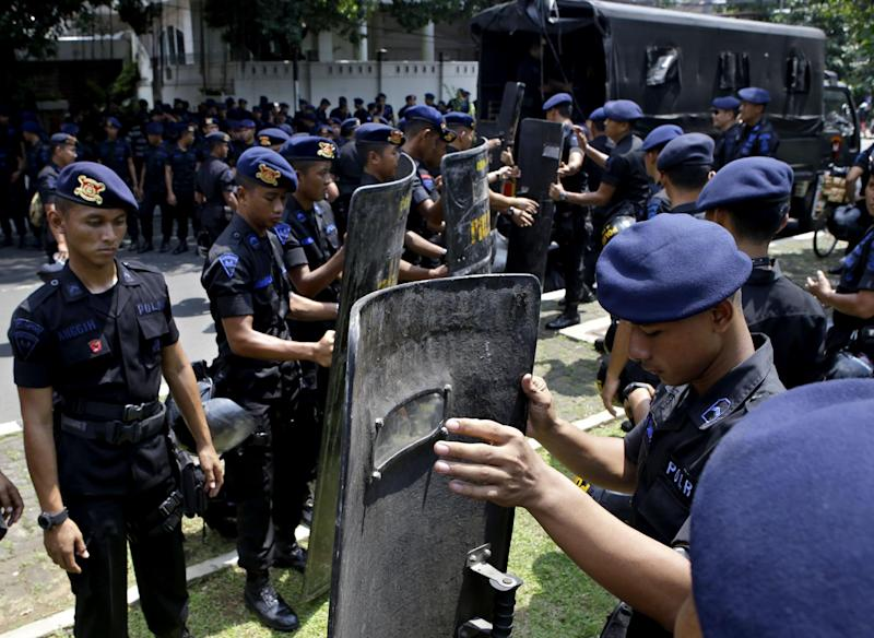 In this Friday, May 3, 2013 photo, police officers are deployed outside the embassy of Myanmar to anticipate a planned Muslim hardliner protest and to provide extra security after the police revealed a plot of a terror attack on the premise on the Facebook page of a suspected militant, in Jakarta, Indonesia. The use of social networking to groom potential attackers is posing a new challenge to authorities in the world's most populous Muslim country that has been struggling to eradicate militant groups. (AP Photo/Dita Alangkara)